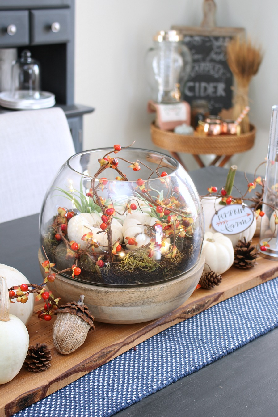 LIghted fall terrarium. Pumpkins, bitter sweet, and twinkle lights in a glass terrarium. Perfect for fall decor.