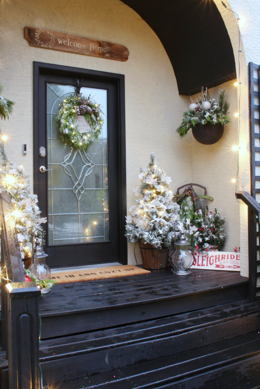 Beautiful Christmas front porch with flocked trees and hanging baskets.