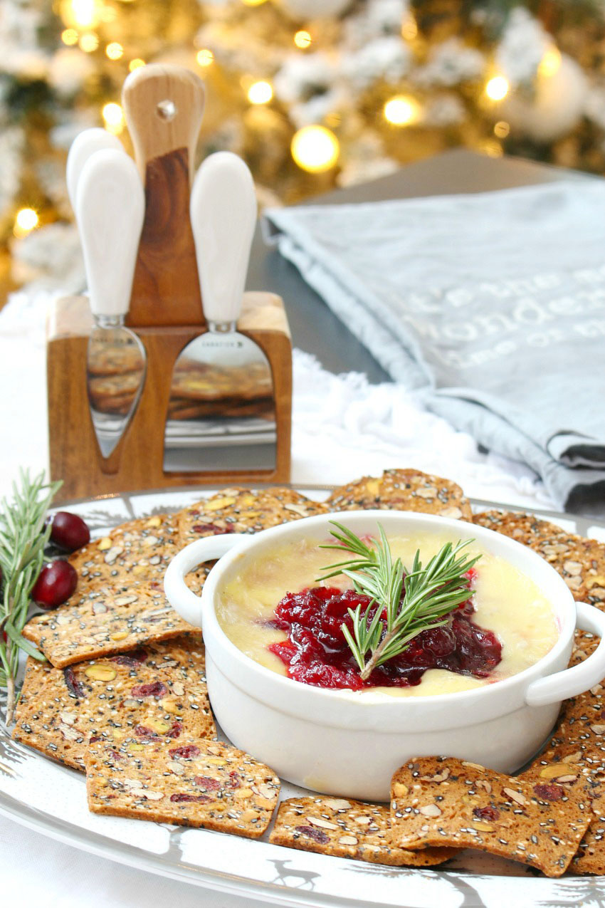 Cranberry baked brie served with cranberry crackers on a Christmas platter.