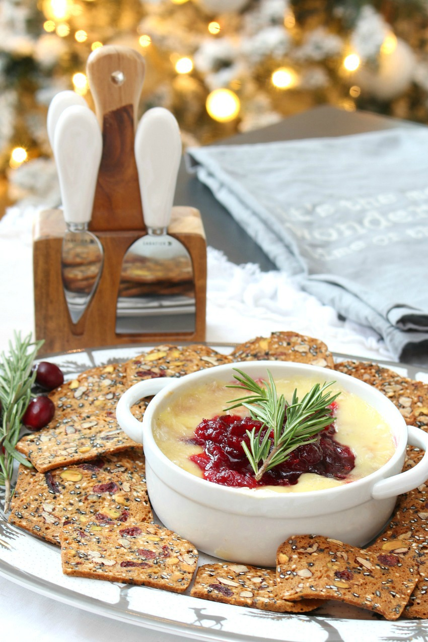 Cranberry baked brie appetizer served with cranberry crackers.