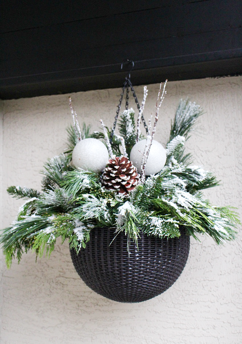 DIY Hanging Christmas Basket. Fresh greenery flocked with a light dusting of snow.