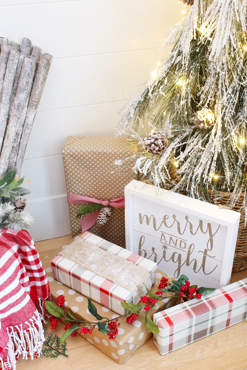 Small flocked Christmas tree with red and white wrapped presents and a Merry and Bright sign.