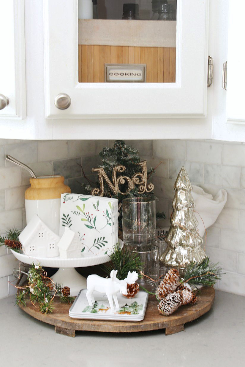 Kitchen Christmas Decorations. White kitchen dressed in frosted greens for a festive touch. Cute Christmas display.