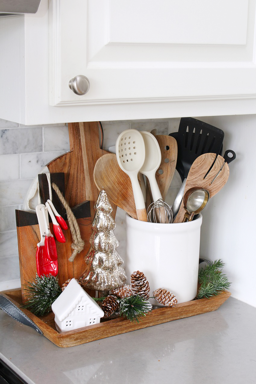 Kitchen Christmas Decorations. White kitchen dressed in frosted greens for a festive touch. Display little vignettes on tray so the kitchen doesn't look so cluttered.