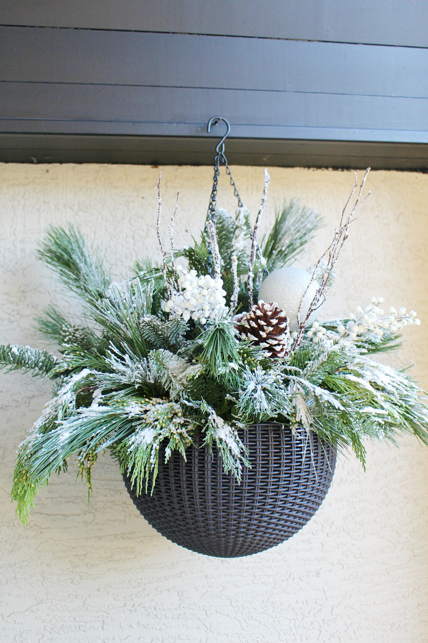Quick and easy DIY outdoor hanging baskets. A mix of fresh greenery, pinecones, and berries with a light flocking of snow.