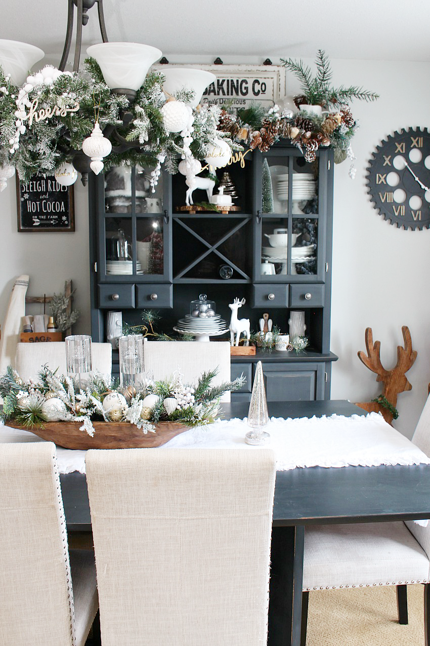 Beautiful farmhouse Christmas dining room with a snowy, winter wonderland feel. Decorated in white, greens, and metallics for that magical Christmas look.