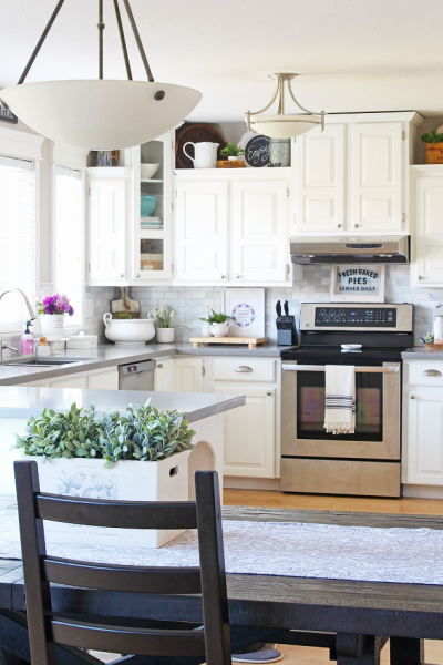 White farmhouse style kitchen with quartz countertops.