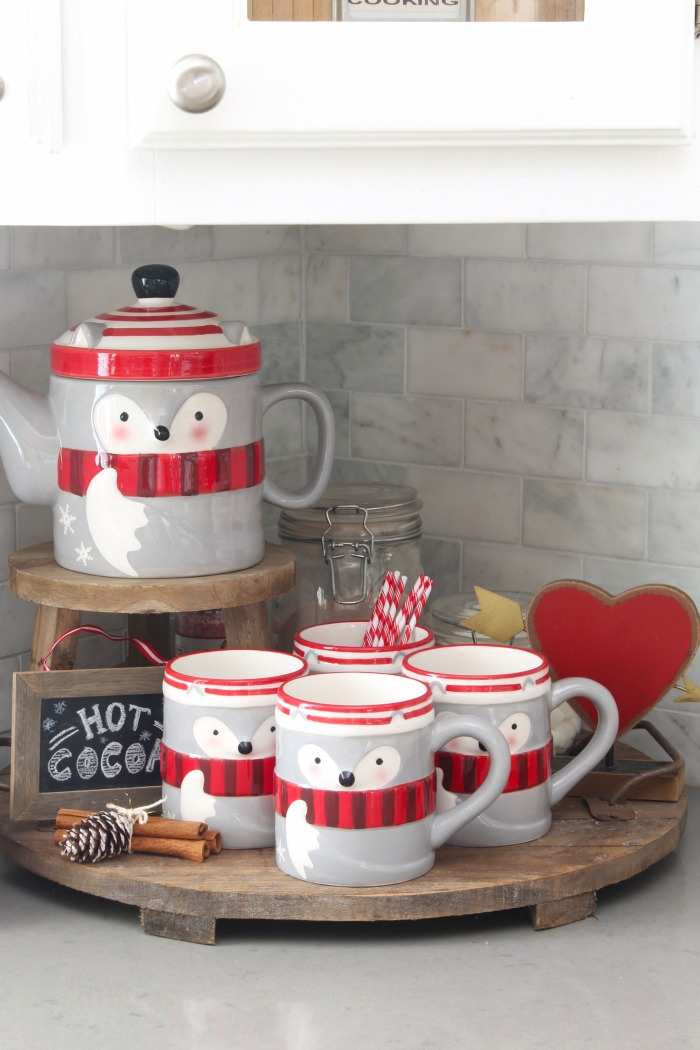 Cute Valentine's Day hot chocolate bar with a raccoon mug set and mason jars for hot chocolate ingredients.