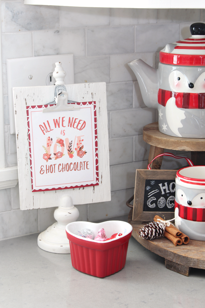 """All We Need is Love and Hot Chocolate"" free Valentine's Day printable displayed in a Valentine's Day hot chocolate bar."
