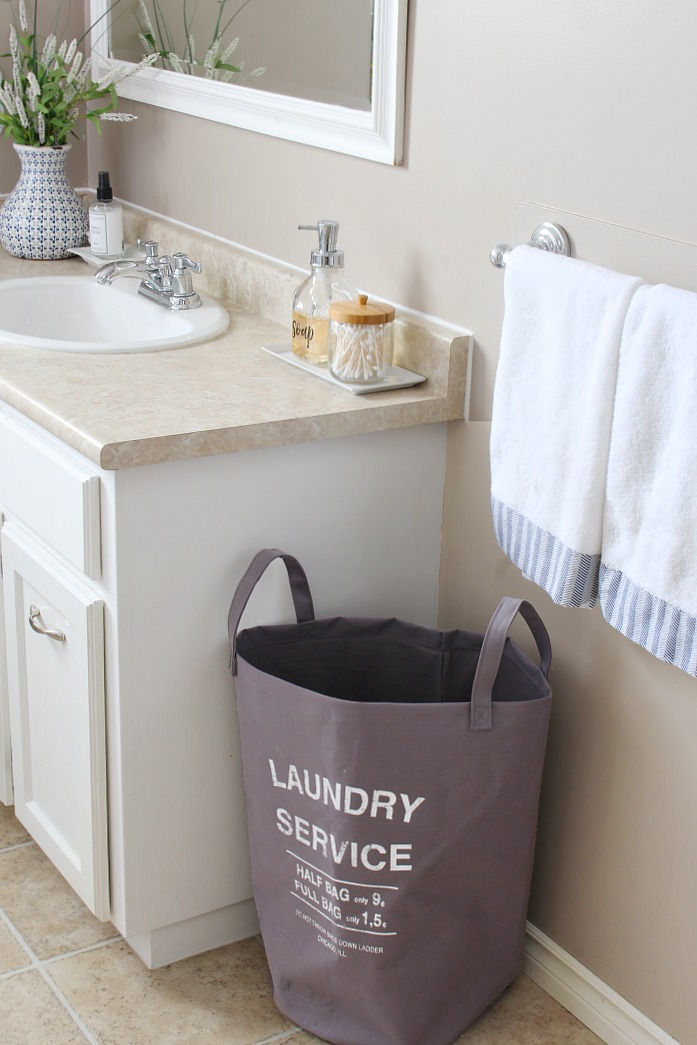 Organized bathroom space with separate laundry hamper for towels.