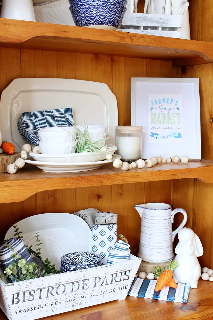 Farmhouse style wooden hutch with white dishes. Styled for spring with blues and greens.