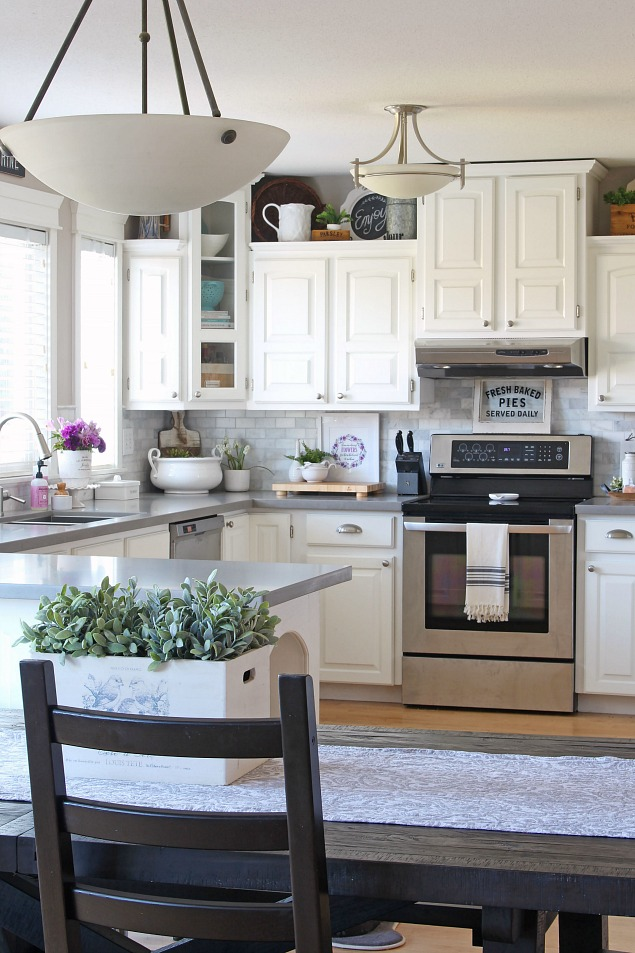Farmhouse style white kitchen with quartz countertops.