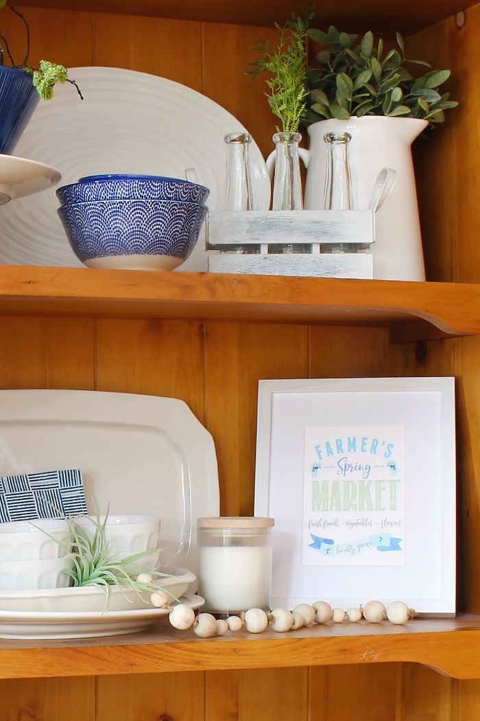 Farmhouse style wooden hutch with white dishes. Styled for spring in with blues and greens.