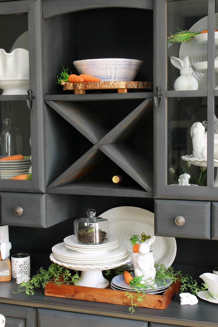 Black painted hutch decorated for Easter with white tableware and white ceramic bunnies.