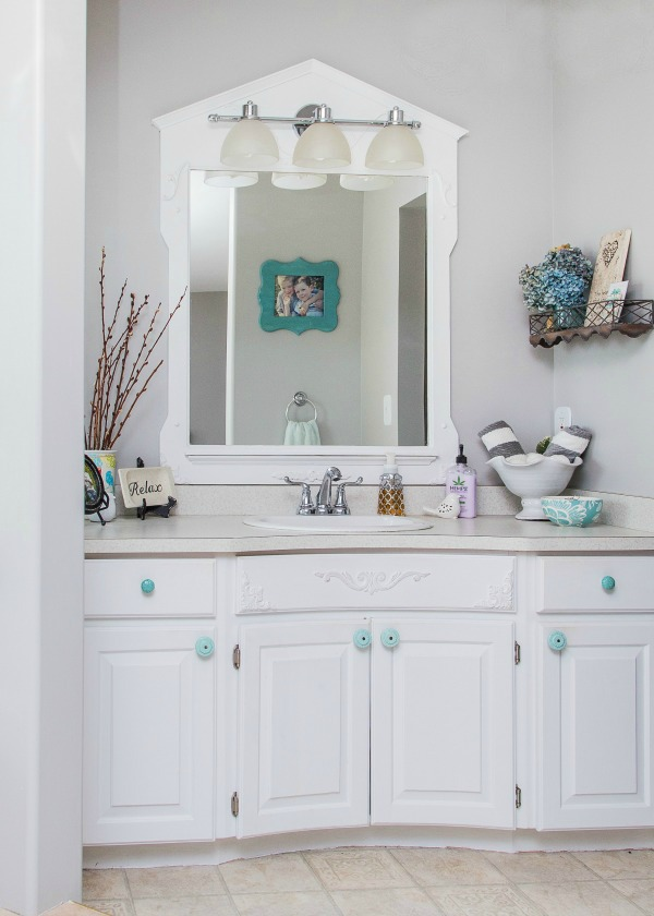 Clean and organized bathroom with white cupboards.