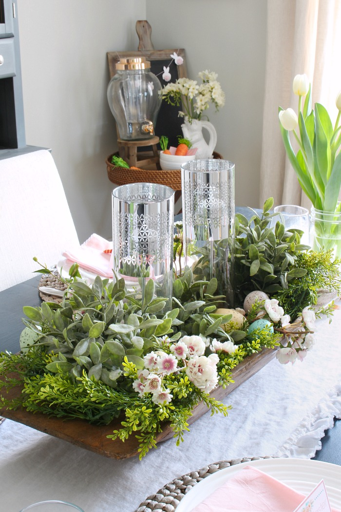 Spring centerpiece using a dough bowl, faux greenery, and flower stems.