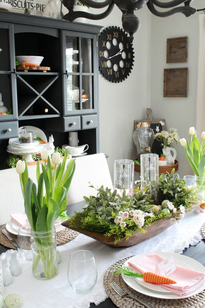 Spring decorations with a large dough bowl centerpiece filled with flowers.