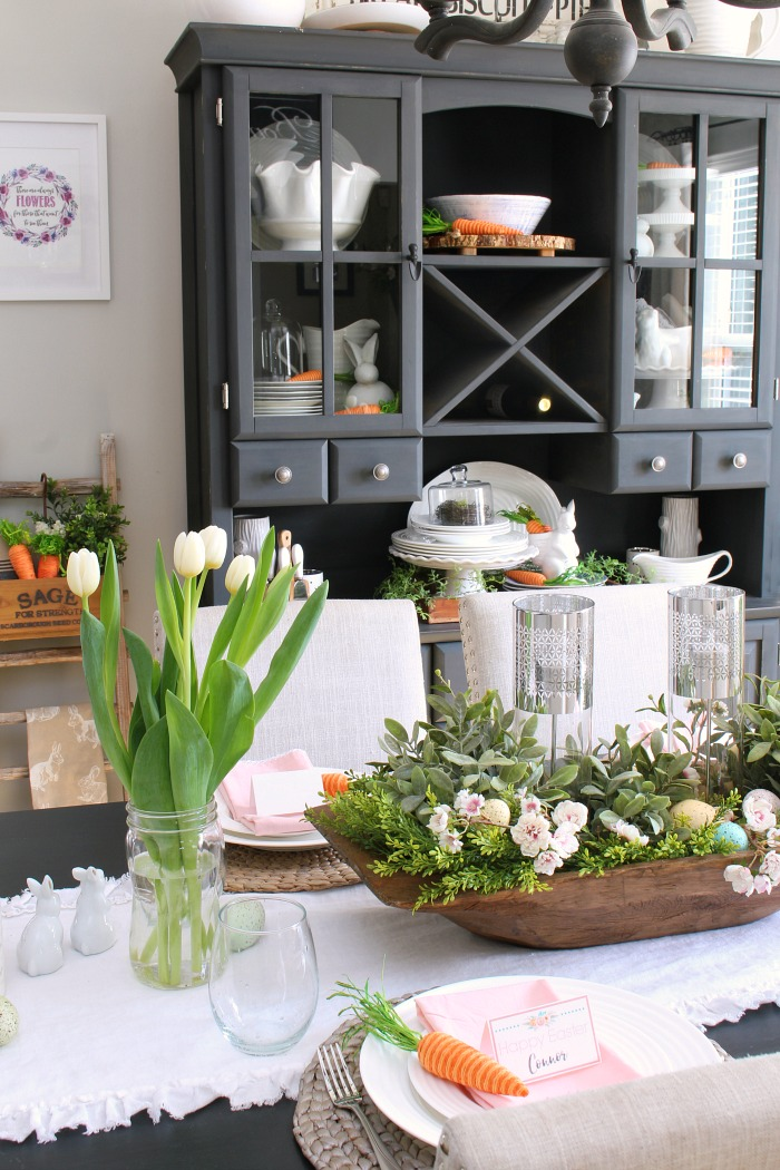 Easter tablescape with dough bowl centerpiece, tulip, and black hutch.