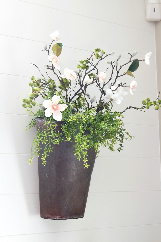 Pretty hanging bucket filled with faux flower stems and greens.