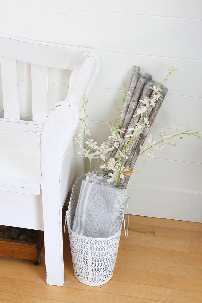 How to add spring to your front entry. Basket filled with faux branches and flower stems.