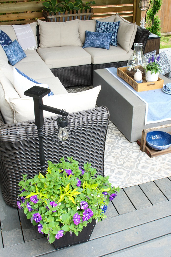 Summer patio with flower planter and DIY wooden holder with hanging lantern.