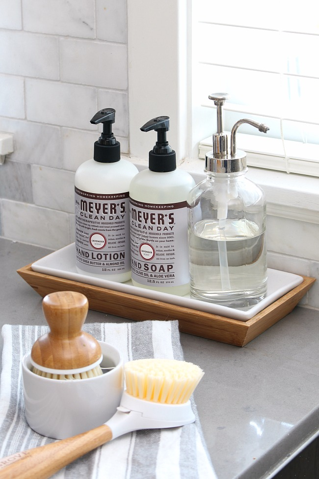 Mrs. Meyers hand soap and hand lotion on a tray beside the sink.
