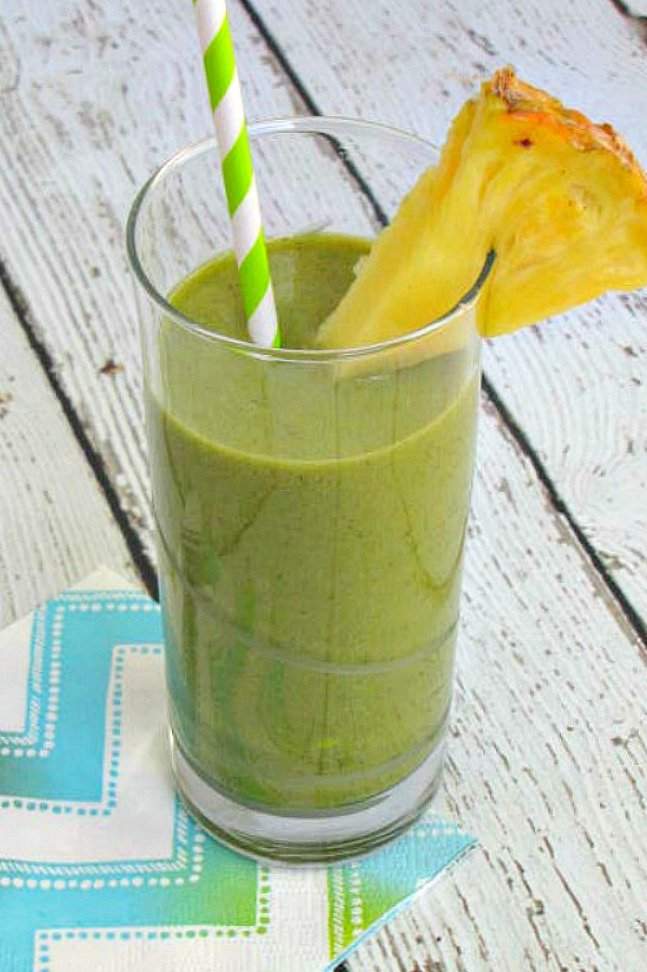 Green smoothie garnished with pineapple.