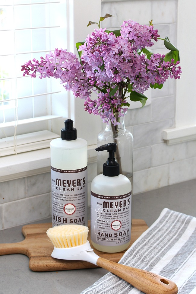 Mrs. Meyers dish soap and hand soap displayed on a wooden cutting board beside the sink.