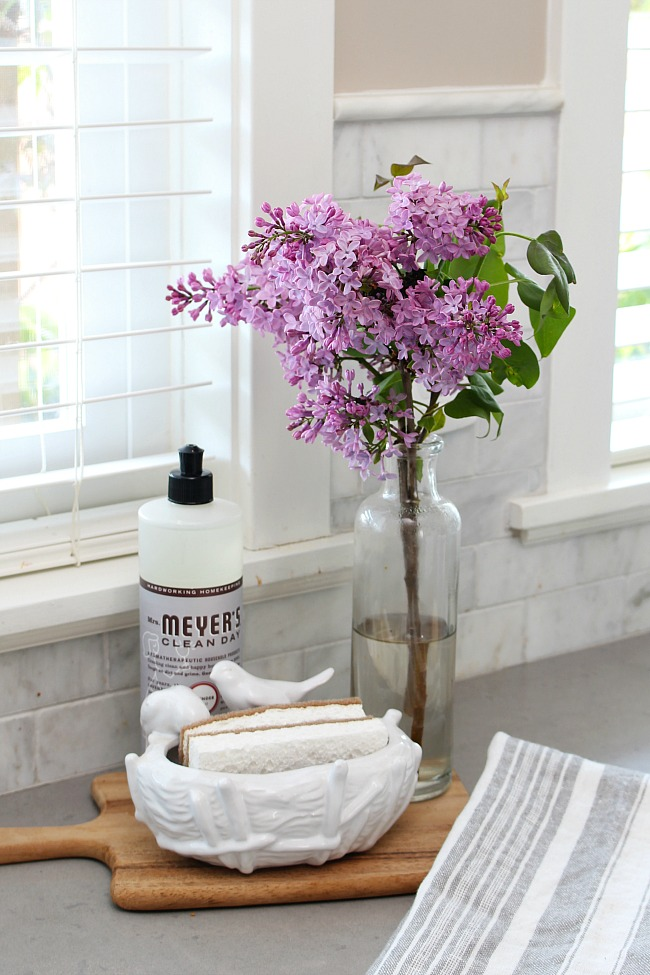 Lilacs with cleaning products displayed on a wooden cutting board.