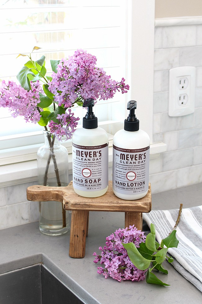 Mrs. Meyer's hand soap and hand lotion displayed on a wooden stand beside the sink.