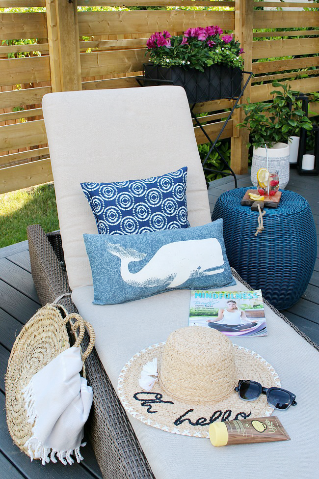 Sun protection tips. Lounge chair with navy pillows and straw hat.