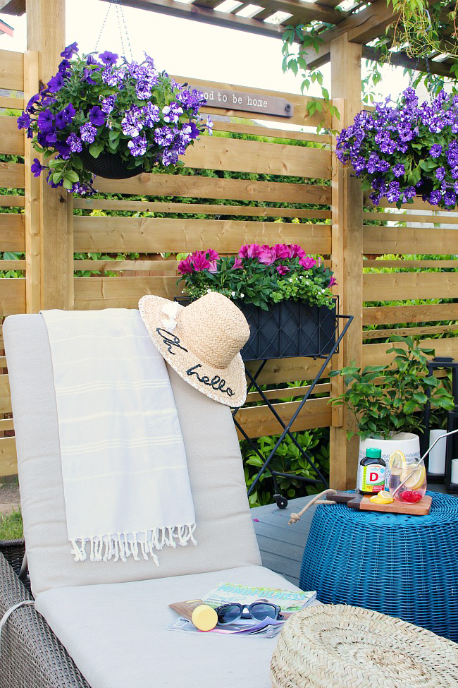 Lounge chair with navy pillows and straw hat.