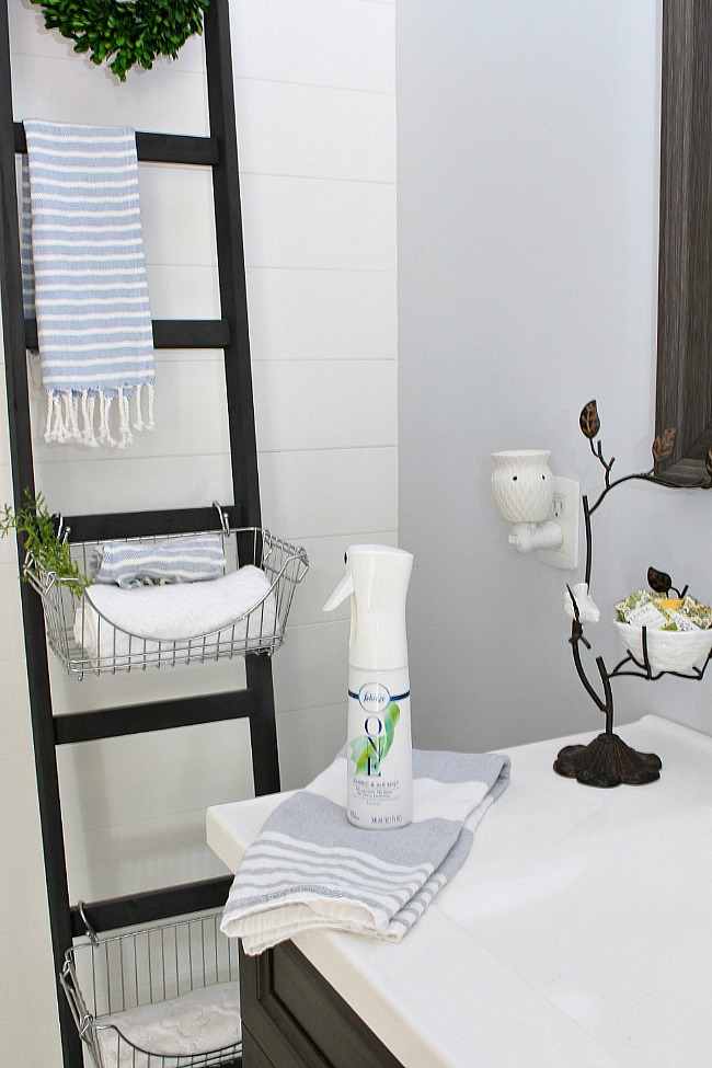 Farmhouse style bathroom with storage ladder and Febreze ONE spray.