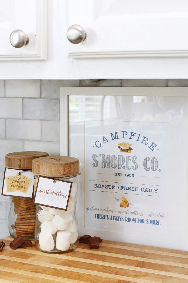 Free s'mores printable framed with s'mores ingredients in labeled mason jars.