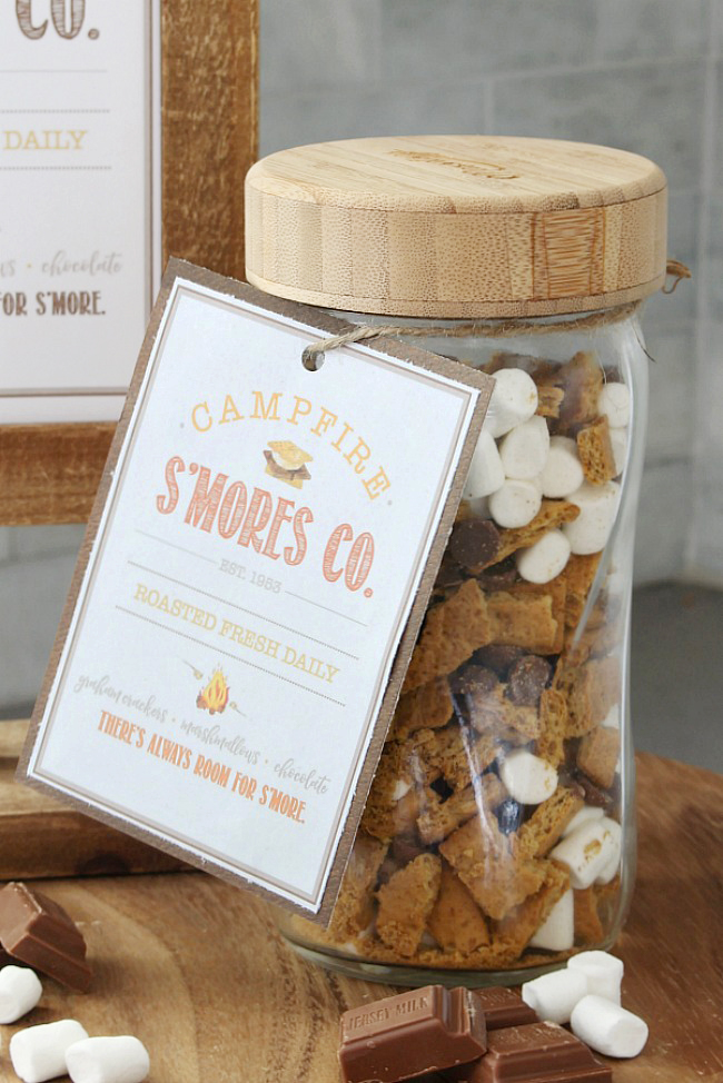 S'mores mix with pieces of graham crackers, mini marshmallows, and chocolate chips. Packaged up in a mason jar with a free printable s'mores tag.
