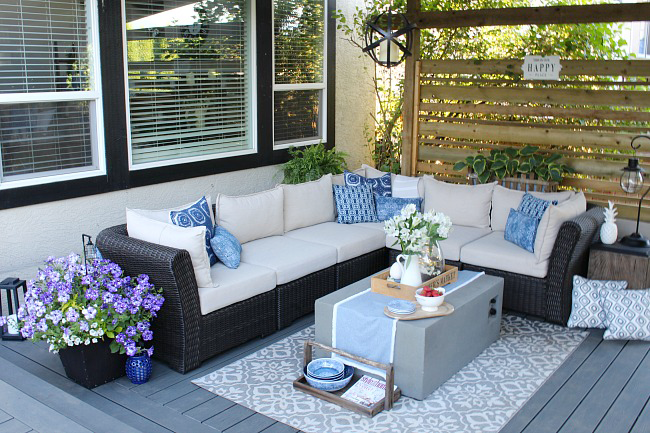 Covered patio with outdoor sofa and fire table.