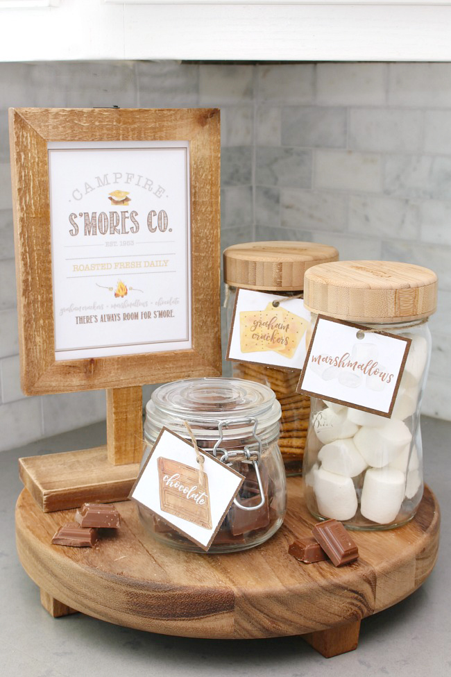 Free s'mores printables in a wooden frame with s'mores ingredients in labeled mason jars.