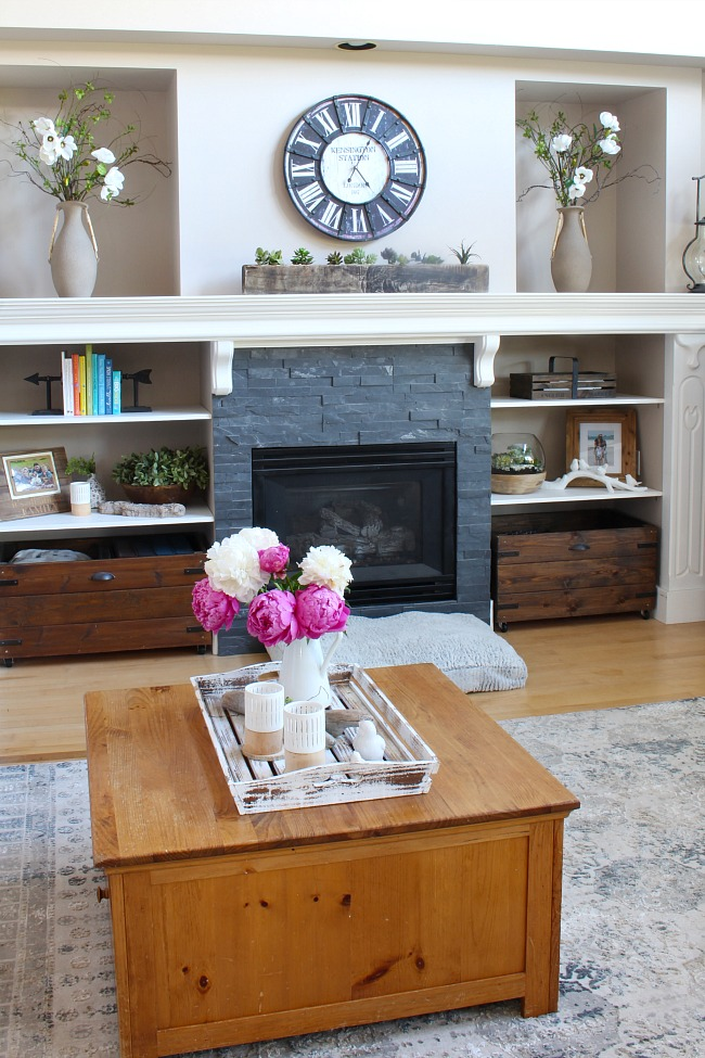 Farmhouse style living room with large white mantel and stone fireplace.