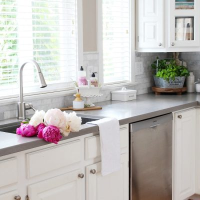 White farmhouse style kitchen with beautiful pink peonies in the sink.