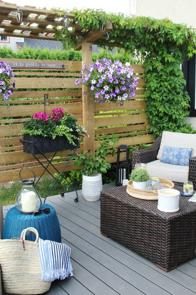 Wooden privacy screen on summer patio decorated with flowers.
