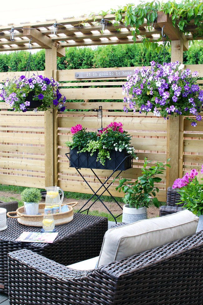 Summer hanging baskets and flower planters on a backyard patio.