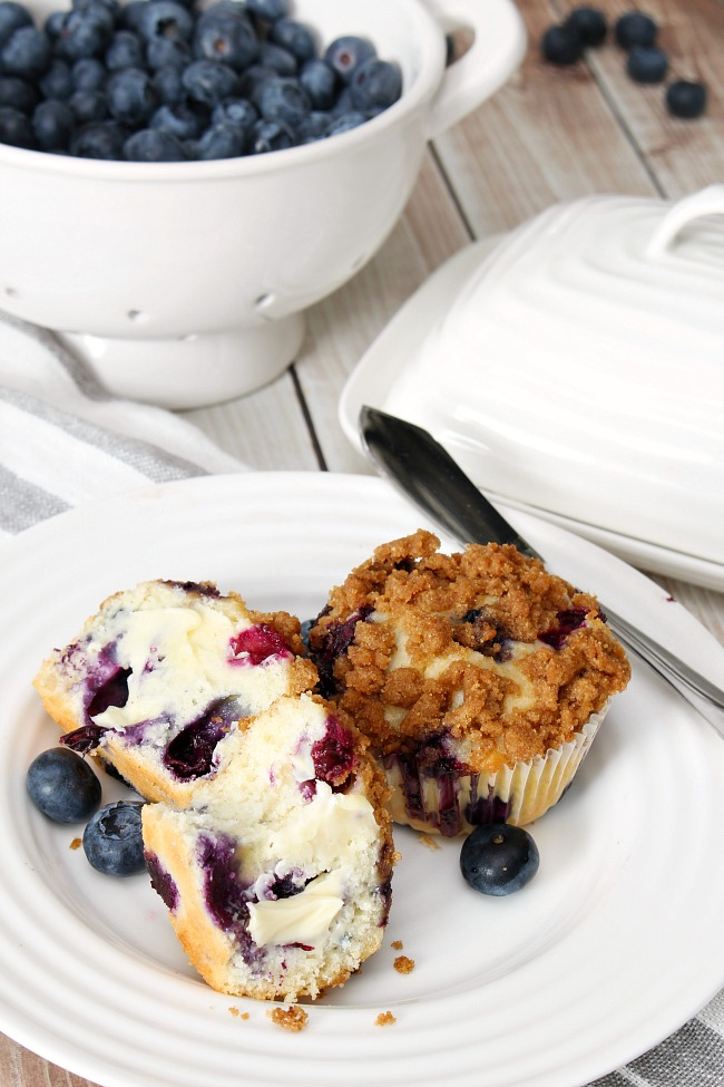 Blueberry muffins on a plate with butter.