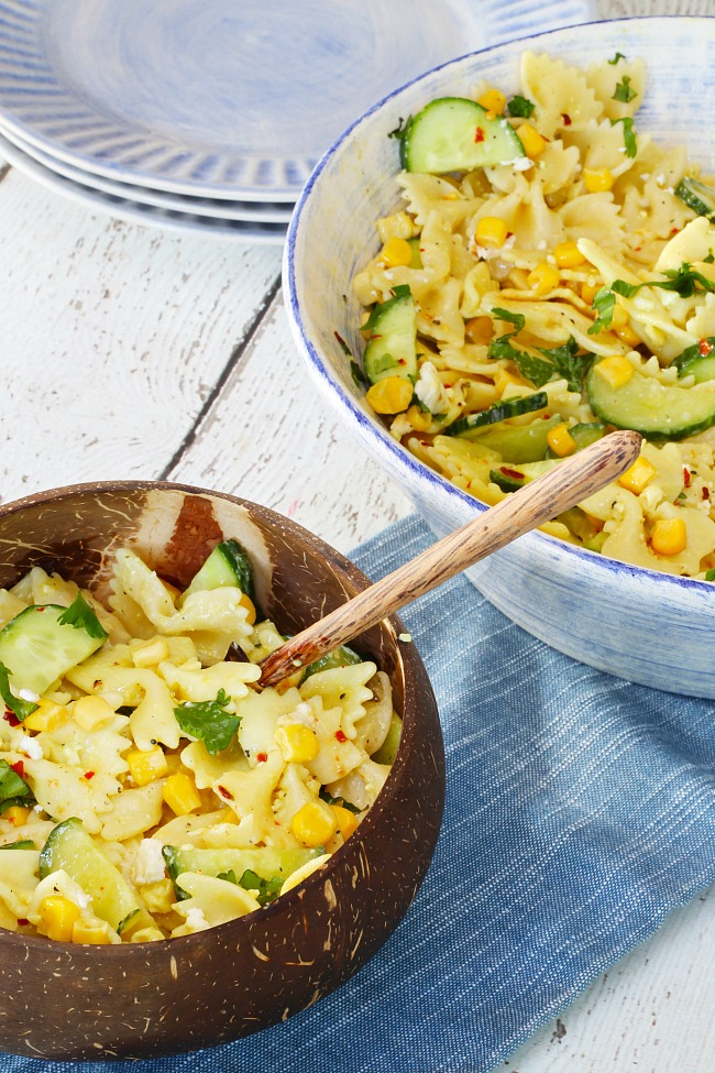 Cucumber and sweet corn pasta salad served in a coconut bowl.