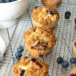 Blueberry muffins with a streusel topping on a cooling rack.