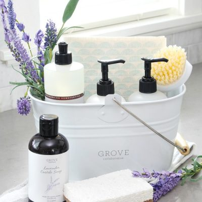 White cleaning caddy with Mrs. Meyers cleaning products in lavender and some lavender castille soap from Grove Collaborative.