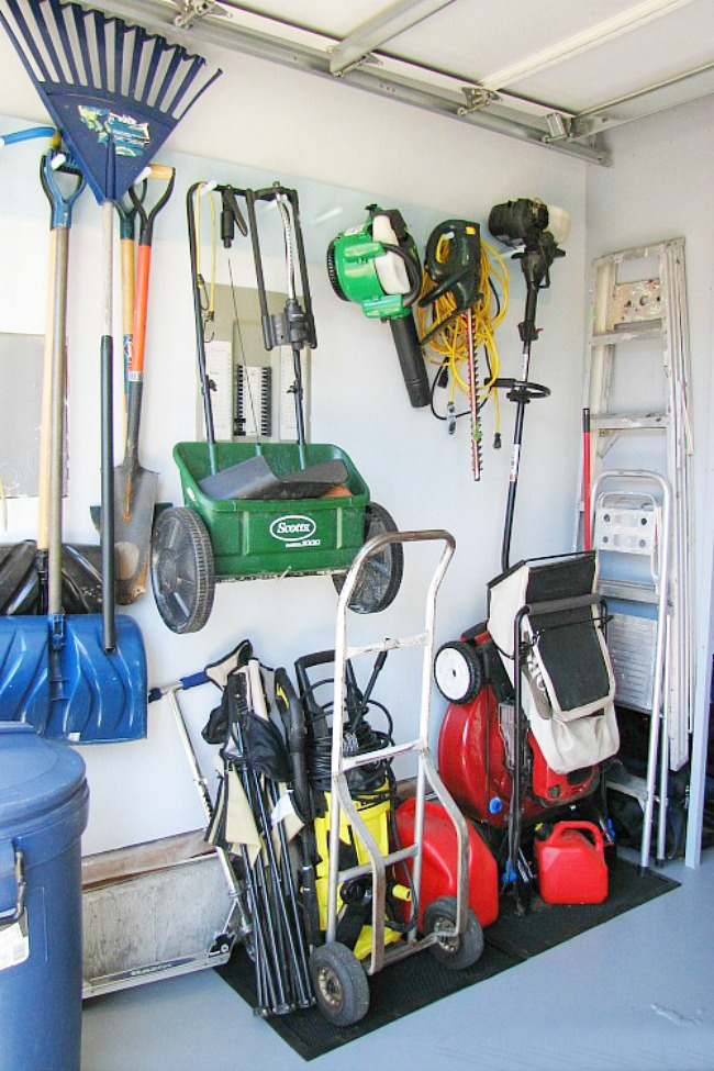 Organized garage space for yard equipment using wall hooks.