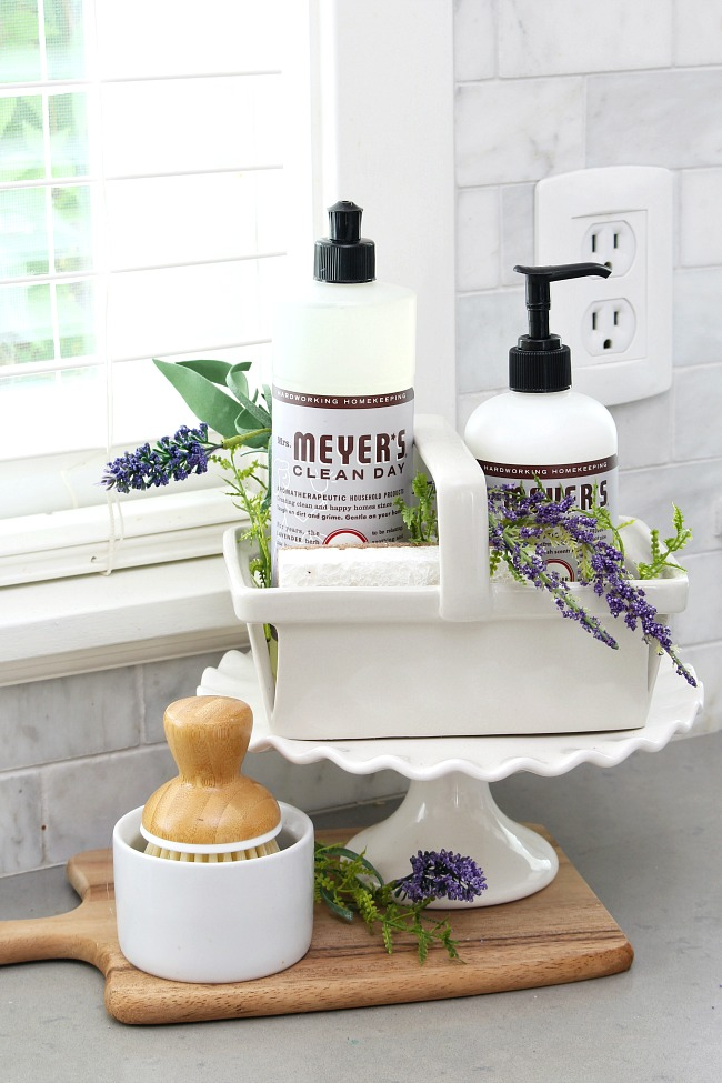 Mrs. Meyers lavender dish soap, hand soap, and hand lotion displayed on a cake stand by the kitchen sink.