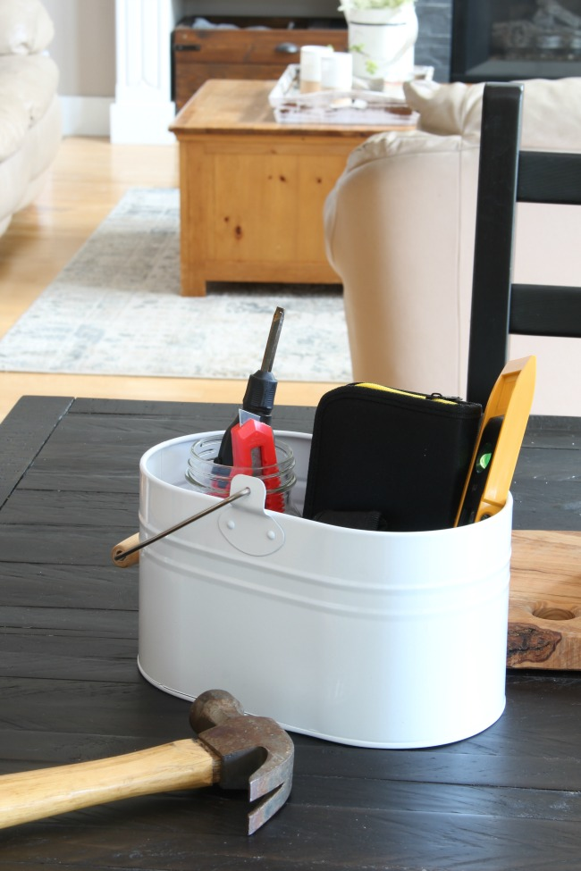 How to Use a Cleaning Caddy to Get Organized. White cleaning caddy filled with basic household tools - tape measure, hammer, multi-head screwdriver, etc.