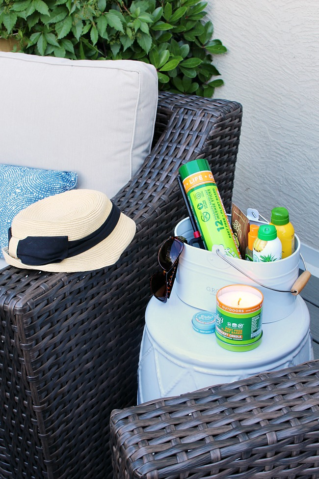 How to use a cleaning caddy to get organized. White cleaning caddy with outdoor summer basics - sunscreen, aftersun, insect repellant, citronella candles, a lighter, etc.