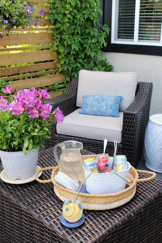 Summer patio with a personal drink caddy filled with drinks and fresh fruit in a mason jar.